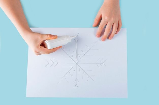 Concept of diy and kid's creativity. step by step instruction: how to make drawing of snowflake with glue and salt. step 3 child's hands apply glue to drawing.