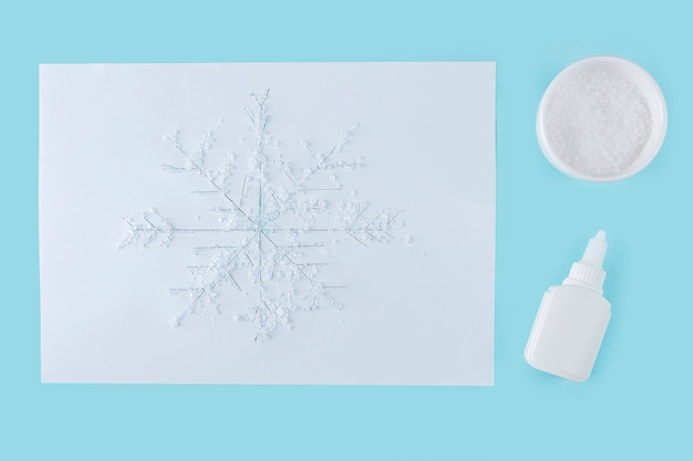 Concept of diy and kid's creativity. step by step instruction: how to make drawing of snowflake with glue and salt. step 4 drawing of snowflake poured with glue and sprinkled with salt.