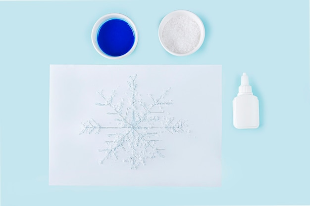 Concept of diy and kid's creativity. step by step instruction: how to make drawing of snowflake with glue and salt. step 4 drawing of snowflake poured with glue and sprinkled with salt