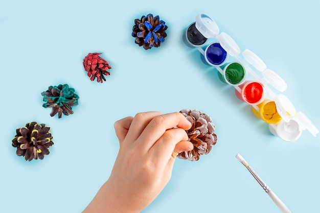 Concept of diy and kid's creativity. step by step instruction: painting pine cone. step 2 child's hands paint pine cone with white paint. children christmas craft