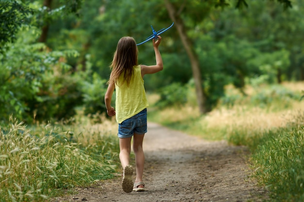 The concept of dreams and travel. happy girl kid playing with toy airplane in summer on nature.