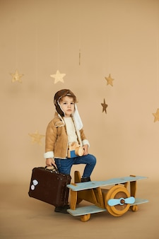 Concept of dreams and travels. pilot aviator child with a toy ai