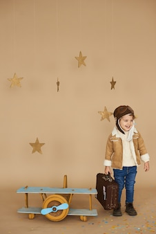 Concept of dreams and travels. pilot aviator child with a toy airplane and suitcase plays in a beige