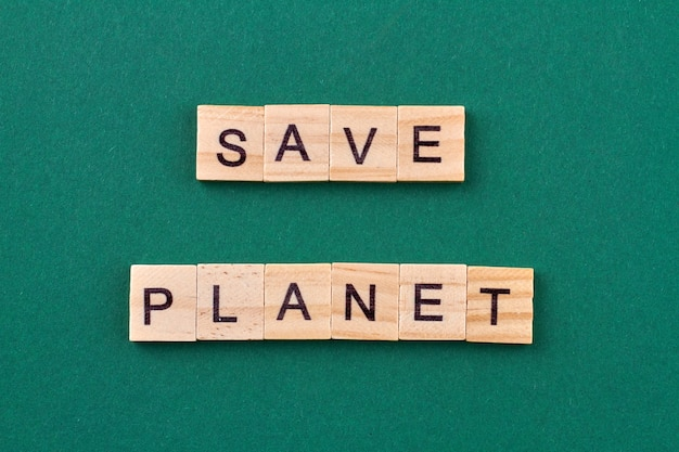 Concept of ecology concern. text save planet written with wooden cubes isolated on green background.