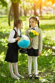 Concept - education. back to school. two cheerful caucasian girls schoolgirls with flowers and a globe, happy to be returning home after class in class