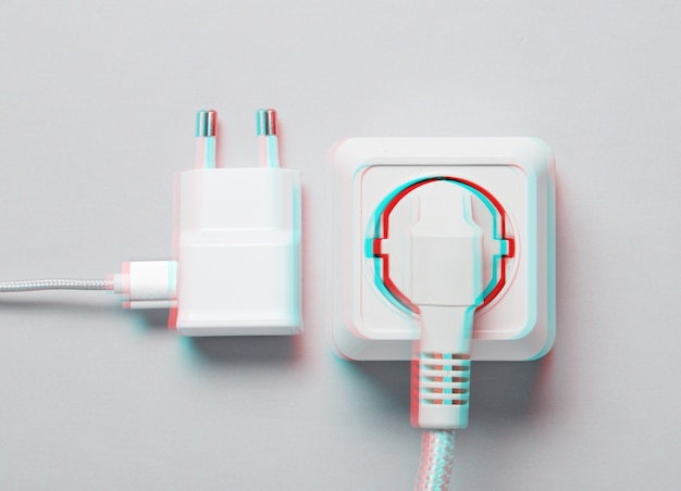 The concept of electrical dependence. the plug is plugged into the power outlet and the charger on a gray background. glitch effect. top view