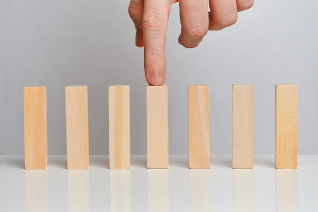 The concept of emphasis on the business process. hand holds wooden blocks on a white space.