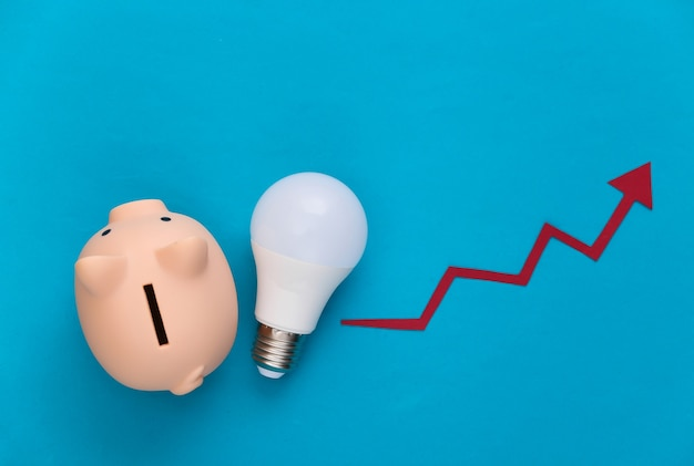 The concept of energy and money saving. growth arrow tending up with light bulb and pigy bank on blue