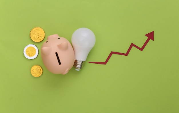 The concept of energy and money saving. growth arrow tending up with light bulb and pigy bank with coins on green