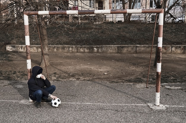Concept of epidemic and quarantine - a boy with a face mask and a ball alone on the sports area in the city