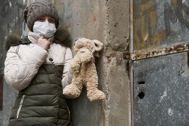 Concept of epidemic and quarantine - a girl with a face mask and a cuddly toy alone on the street in the city