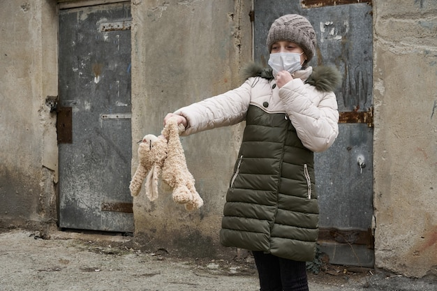 Concept of epidemic and quarantine - a girl with a face mask and