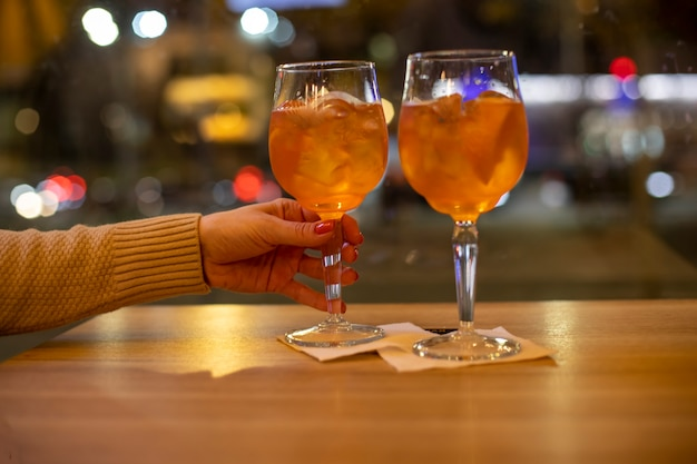Concept of evening time in bar of two people. female hand holds coctail, another coctail is on the table.
