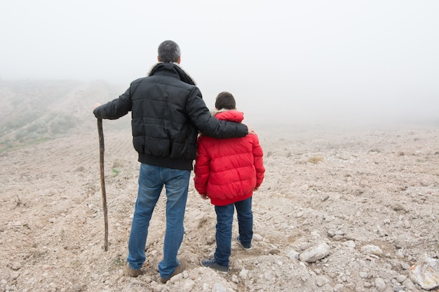 Concept of family escaping.  father and son in a mountain road with fog.