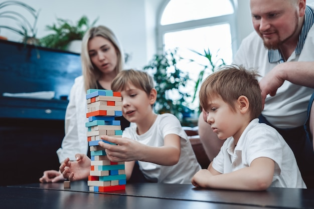 Concept of family they spend time together and have fun. joyful brothers and their parents play jenga game in living room.