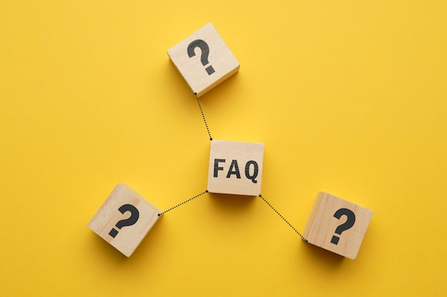 Concept faq - abstract signs on wooden cubes with yellow space.