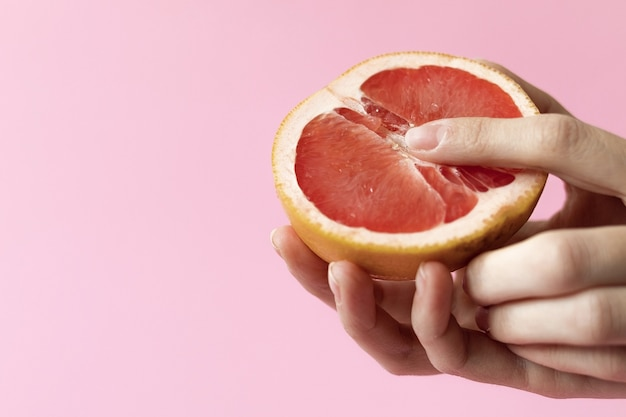 Concept of female sexuality and arousal, half grapefruit on table