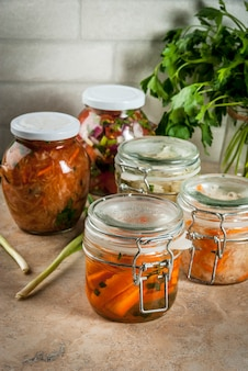Concept of a fermented meal. home canned food and billets. vegan food. vegetables. cans of canned salsa, sauerkraut, marinated carrots, kimchi and cauliflower broccoli. home kitchen table.  copyspace