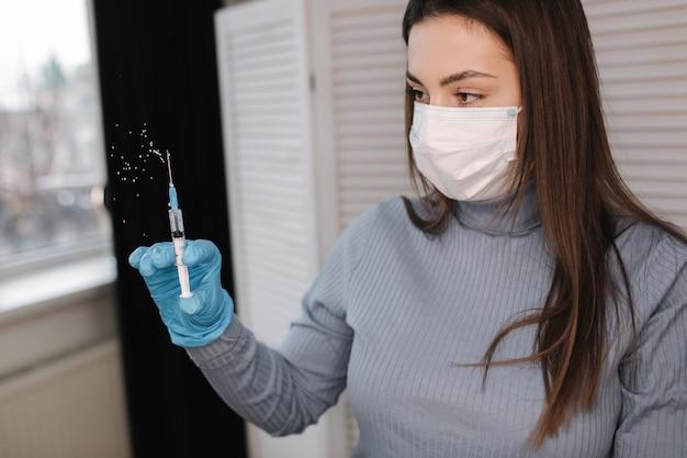 液体ワクチンの注射器を保持しているウイルスcovidコロナウイルス女性との概念の戦い