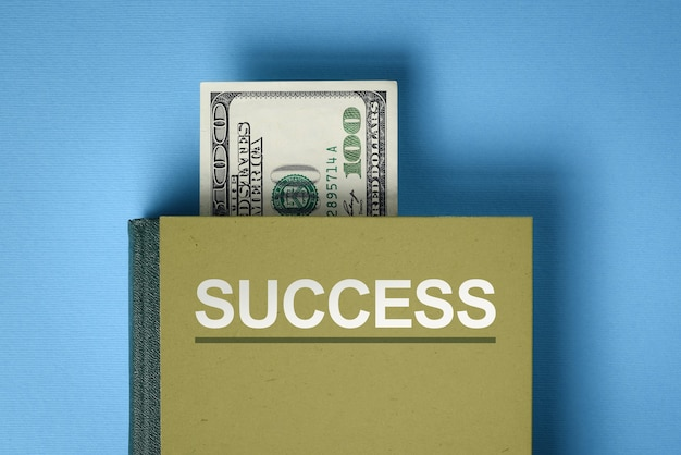 The concept of financial success. a book with answers to the question: how to make money and invest. dollar banknote between book pages (bookmark)