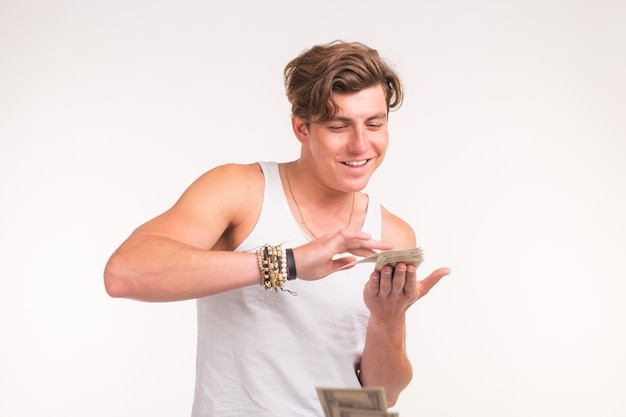 Concept of financial wealth, prosperity and lottery winnings - man throwing away his money on white background.