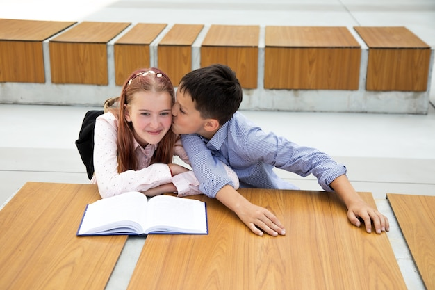 Concept of first feelings, first kiss, school love. boy kisses girl, teenager is very happy and surprised, childhood, school life, lifestyle