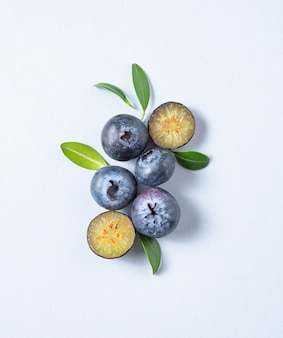 Concept flat lay with a  few juicy blueberries with green leaves on blue background. top view and copy space  image