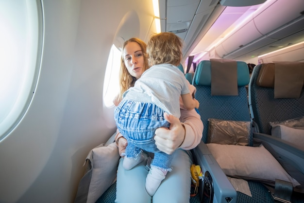 Concept of flight with child little cute toddler jumping on knees young mother in an airplane chair