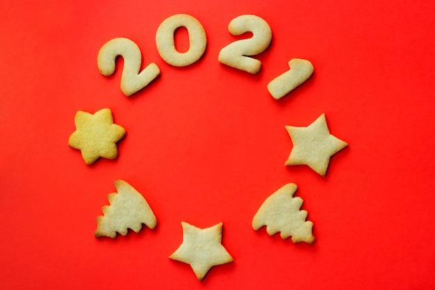 2021年のコンセプト。赤い背景の上のクッキーで作られたクリスマスグリーティングカード。円の形をしたクッキー。上からの眺め、テキストの場所