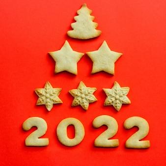 2022年のコンセプト。赤い背景にクッキーで作られたグリーティングクリスマスカード。クッキーのクリスマスツリーの形。上面図、コピースペース Premium写真