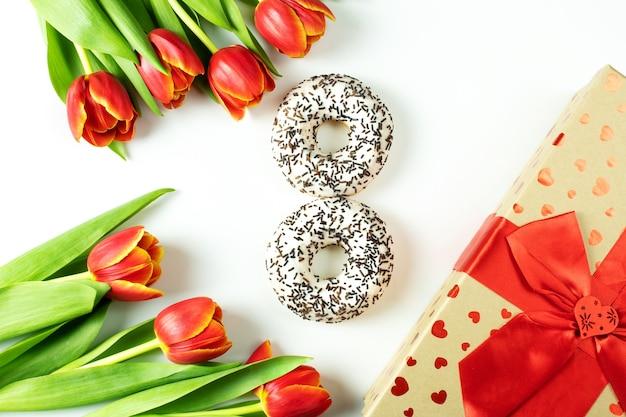 3月8日のコンセプト、女性の日、花の白いドーナツ、花のチューリップ、白い表面に赤いリボンのギフトボックス、上面図、フラットリー