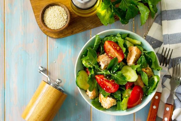 Концепция вкусной и здоровой еды салат из лосося на гриле с огурцами, помидорами, свежей рукколой