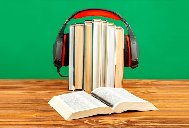 Концепция аудиокниги, стопки книг и наушников