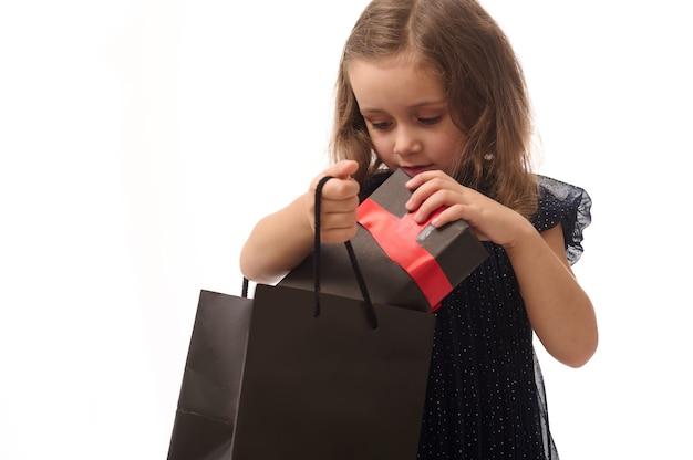 Концепция черной пятницы, изолированный портрет очаровательной девочки в темно-синем вечернем платье, кладет подарок с красной лентой в черный пакет, копирует пространство. концепция покупок, продаж и покупок.