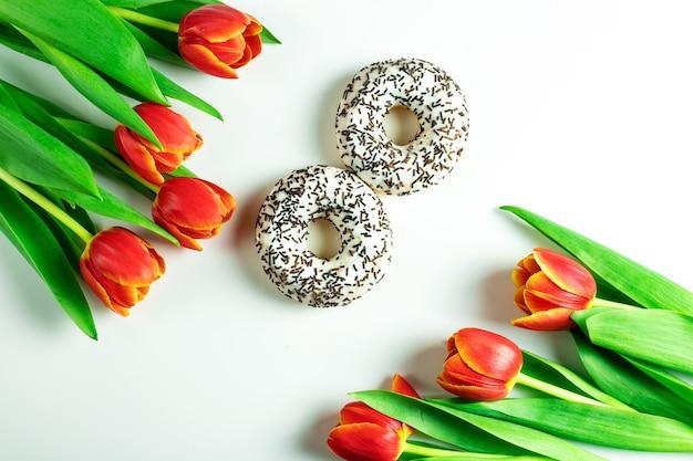 3月8日のコンセプト、女性の日、花と白いドーナツ、チューリップの花、白い表面、上面図