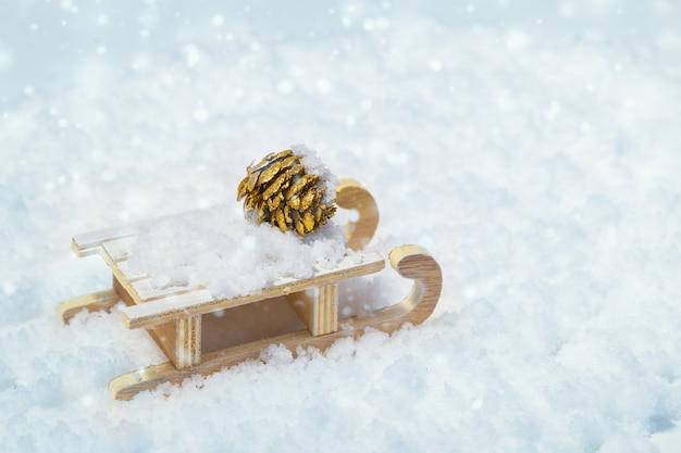 Концепция для нового года и рождества деревянных саней и золотой шишки на снегу