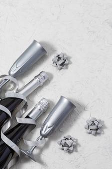 Концепция на новый год, рождество, юбилей, день рождения. праздник или праздник фон с копией пространства. вид сверху на бокалы для шампанского, бутылки и серебряный серпантин.
