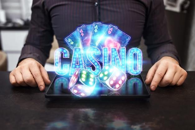 온라인 카지노, 도박, 온라인 머니 게임, 베팅에 대한 개념. 네온 카지노 칩, 카지노 비문, 포커 카드, 주사위가 노트북에서 날아갑니다.
