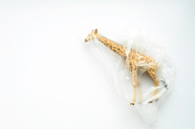 Концепция пластического загрязнения, загрязнения окружающей среды, проблемы экологии. статуэтка жирафа в полиэтиленовом пакете. детская игрушка. плоская планировка, вид сверху