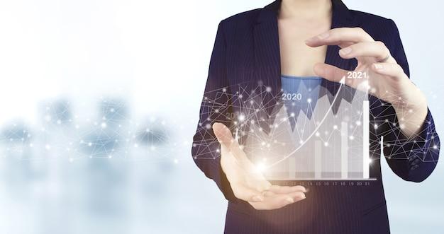 비전 2021-2022에 대한 개념. 사업가 환영 2022년입니다. 두 손은 밝은 배경이 있는 가상 홀로그램 성장 그래프 차트 아이콘을 들고 있습니다. 비즈니스 성장 개념 2022년.