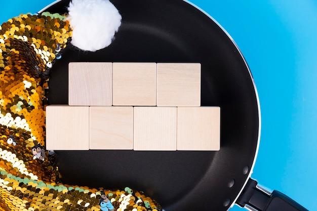 フライパンとサンタクロースの帽子にある7つの木製の立方体にテキストを書くための概念。スペースをコピーします。
