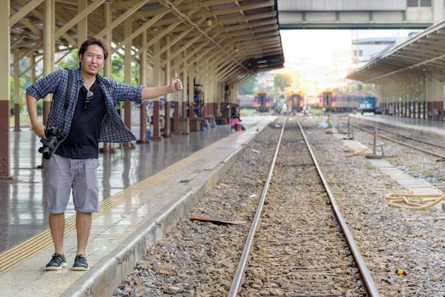 개념 자유형 여행 : 아시아 여행자 남성은 기차가 역에 도착하기를 기다리는 동안 철도 트랙에서 히치 하이킹 표지판으로 엄지를 사용합니다.
