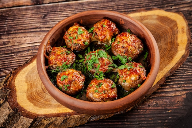 The concept of georgian cuisine. baked mushrooms champignons with meat and cilantro. serving dishes in a restaurant in a plate made of red clay. on a wooden background. copy space