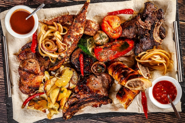 Concept of georgian cuisine. large meat board with shashlik, roasted meat, french fries, roast lamb and sauce. serving dishes in a restaurant on a pita. top view, copy space