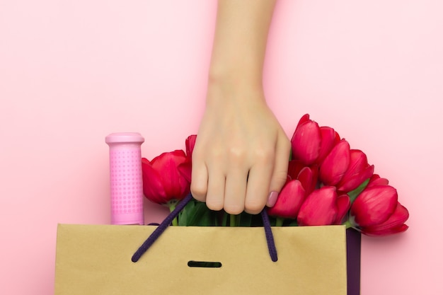 Concept of the gift with wine and red tulips in the paper bag on the pink background. flat lay, copy space. woman hand holds a present to womens day, mothers day, spring concept. flower decoration