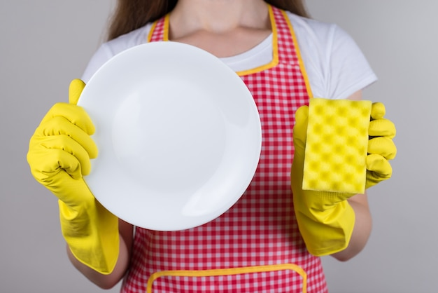 Concept of good detergent. cropped close up  of positive cheerful glad lady wife showing pure clear white plate dishcloth in hands isolated grey wall