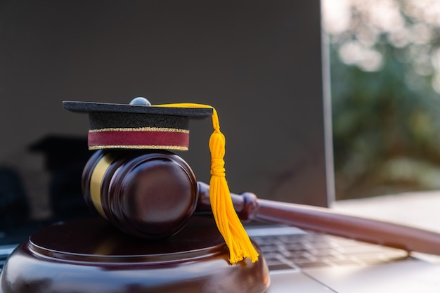 Concept of graduate online study international abroad about jurisprudence laws certificate in university distance education for learning. graduation diploma hat / judge gavel on computer notebook.