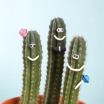 Концепт группы кактусов в цветочном горшке с забавным лицом - образ семьи из мамы, папы и ребенка