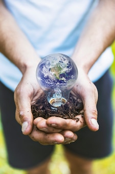 Concept hands holding earth in bulb