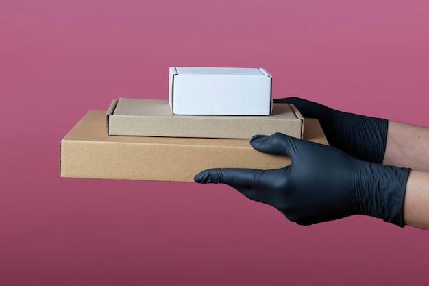 医療用黒い手袋のコンセプトの手は、ピンクの背景に分離されたさまざまなサイズの段ボール箱を保持します。配達、引越し、梱包、ギフト。レイアウト